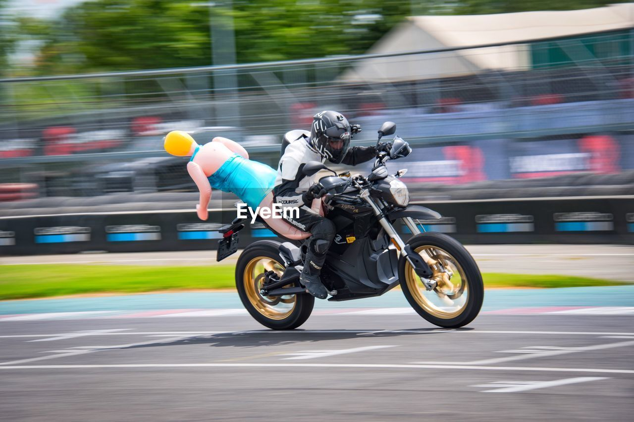 motion, blurred motion, sport, transportation, speed, real people, helmet, sports race, competition, headwear, mode of transportation, full length, on the move, sports helmet, riding, day, road, people, ride, outdoors, skill, crash helmet