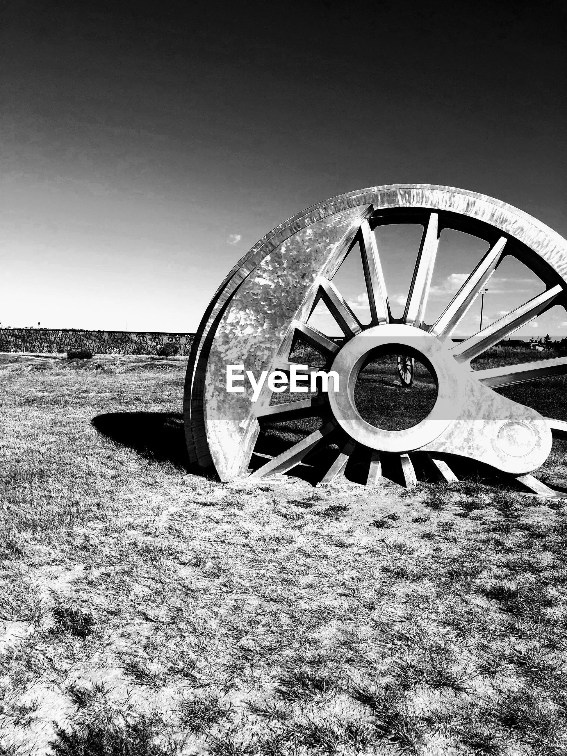 Old abandoned wheel on field against clear sky