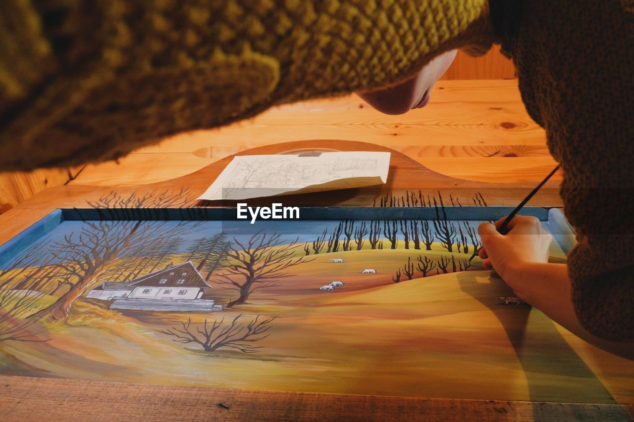 Low Angle View Of Woman Drawing On Canvas In Cottage