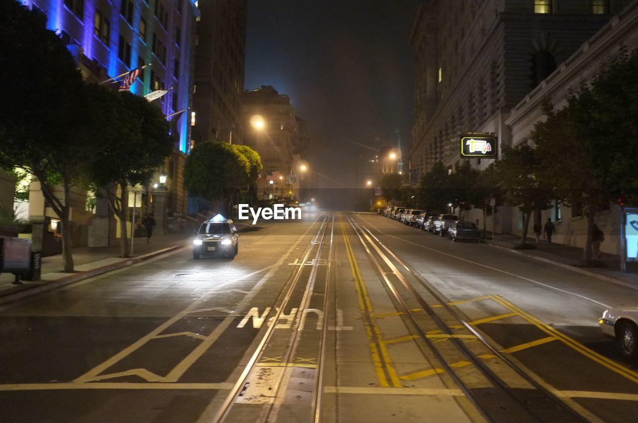 VEHICLES ON CITY STREET AT NIGHT