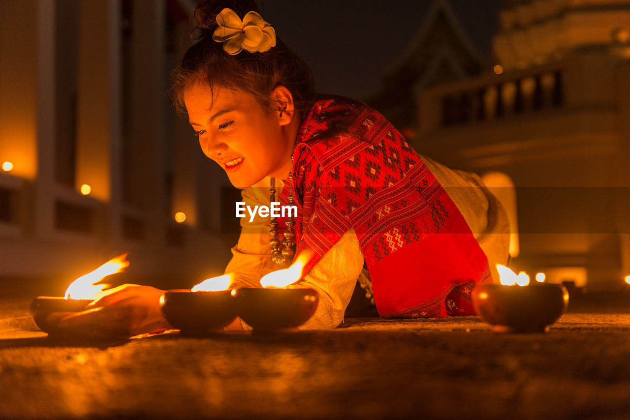 Young Woman Lighting Diya At Night
