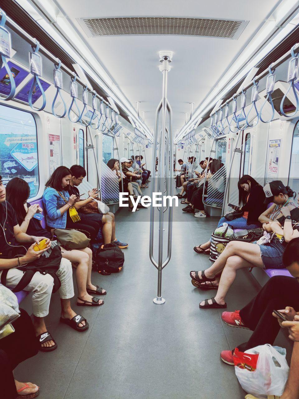 transportation, sitting, vehicle interior, public transportation, real people, large group of people, train - vehicle, mode of transport, men, vehicle seat, women, lifestyles, journey, subway train, indoors, day, people