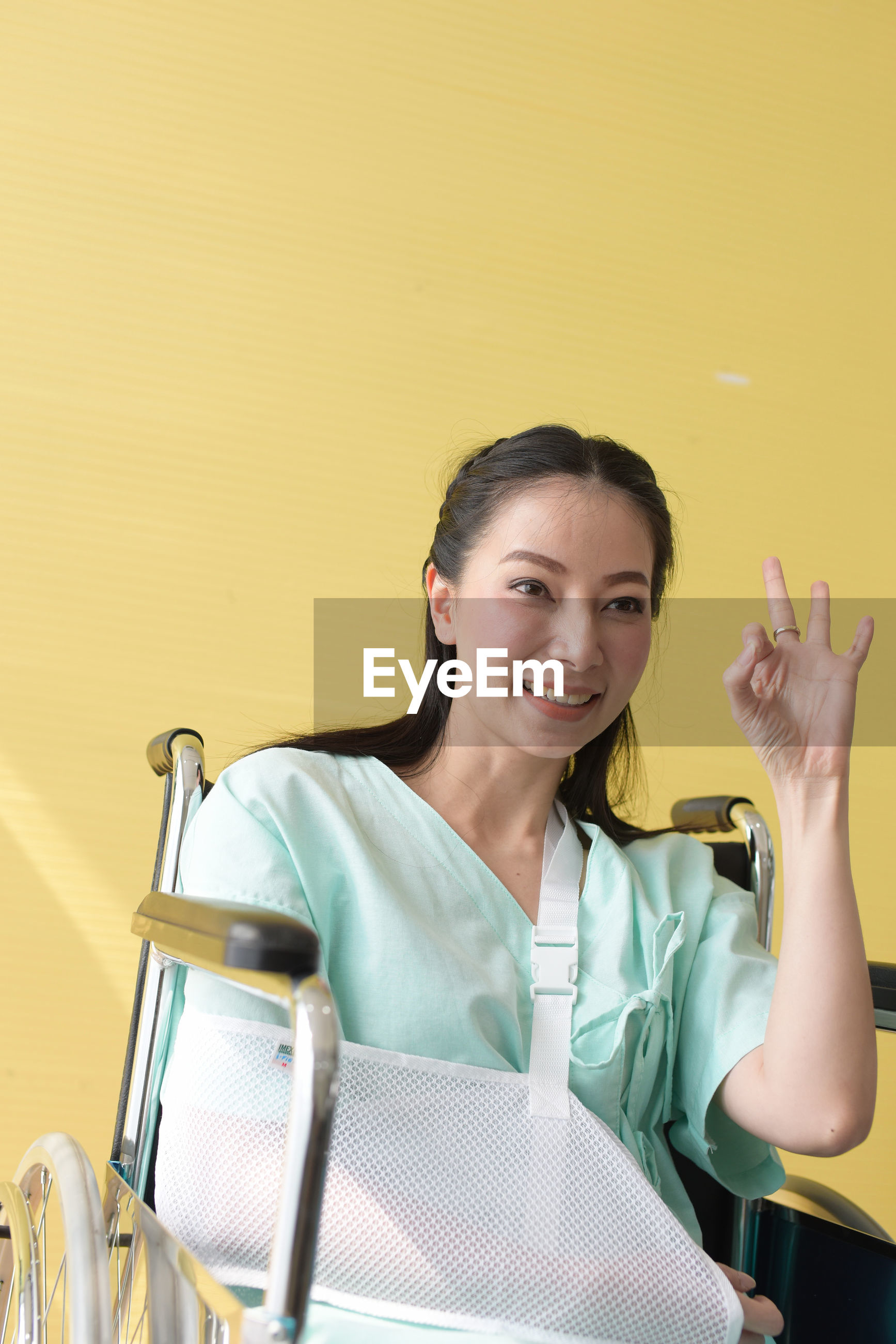 Smiling disabled woman gesturing while sitting on wheelchair against wall