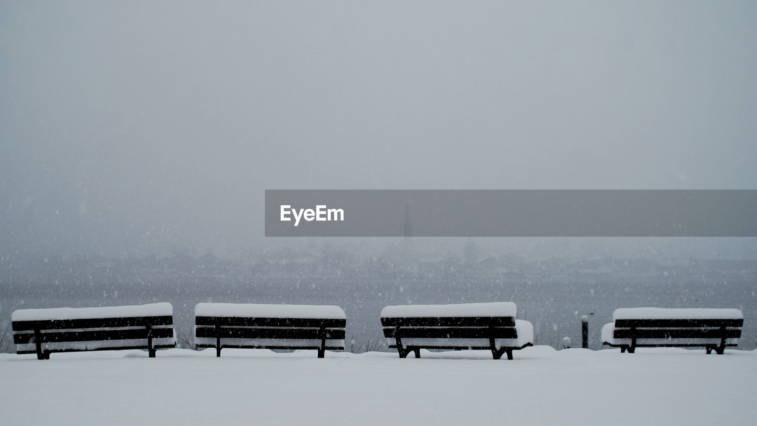 Snow covered benches against sky during snowfall