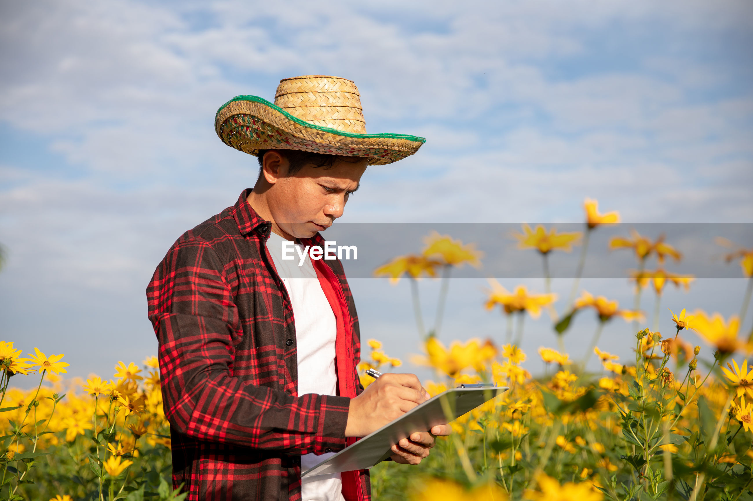 Man writing over paper while standing by flowering plants against sky