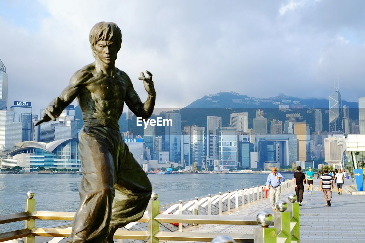 People walking by bruce lee statue at tsim sha tsui against cloudy sky