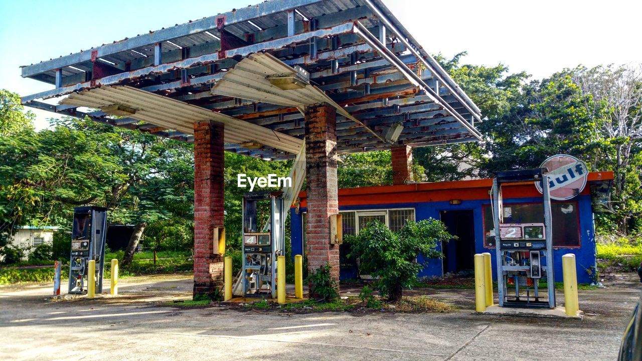 building exterior, architecture, built structure, tree, outdoors, street, gas station, day, no people, fuel pump, gasoline, telephone booth, sky, pay phone