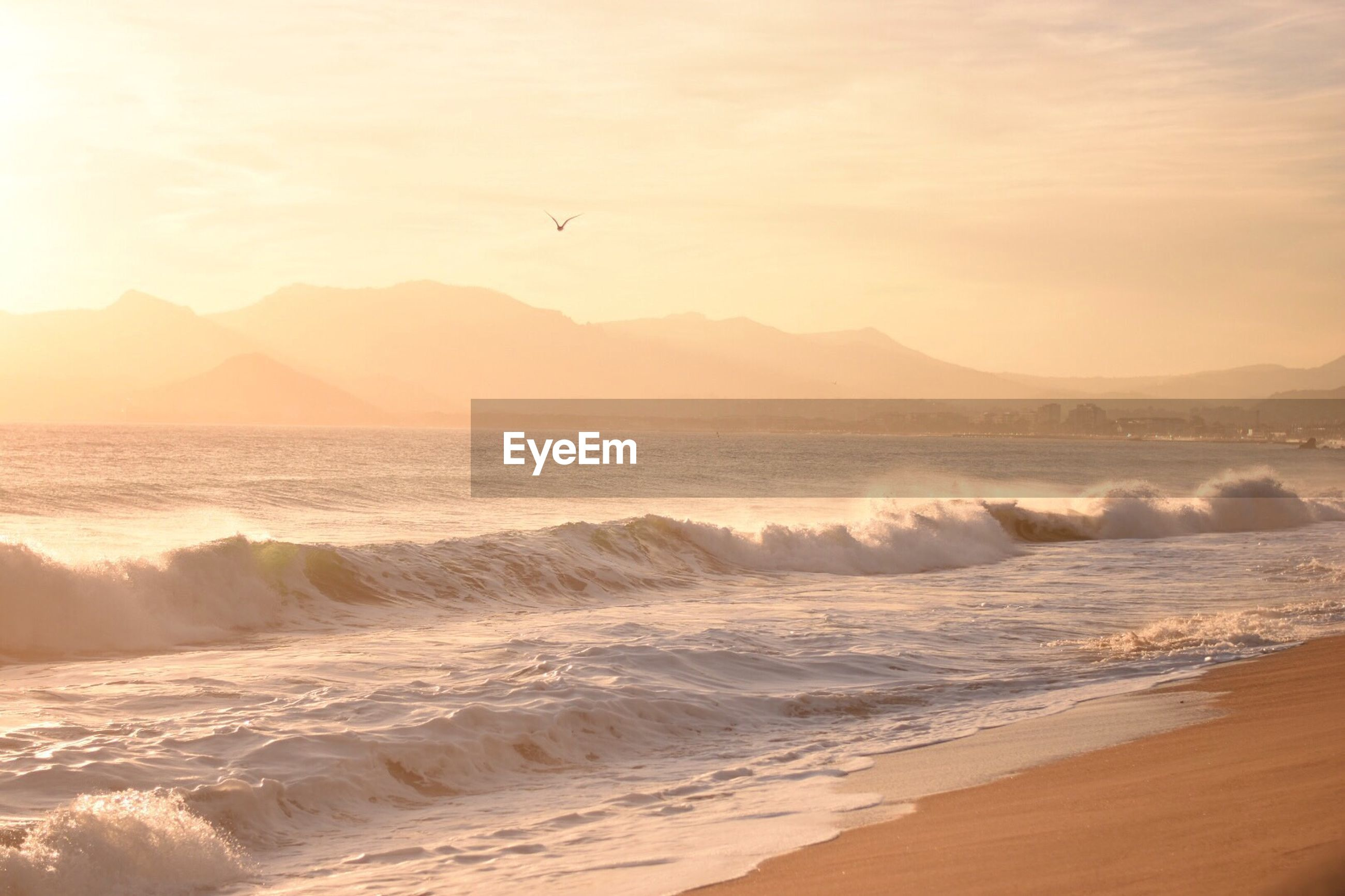 Scenic view of sea by mountains against sky during sunset