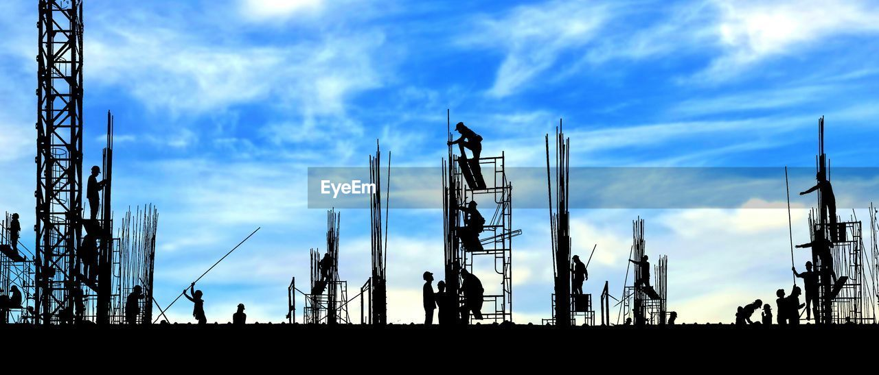 sky, cloud - sky, industry, silhouette, nature, construction industry, machinery, built structure, outdoors, architecture, day, low angle view, crane - construction machinery, development, technology, group of people, construction site, connection, business, global communications, construction equipment