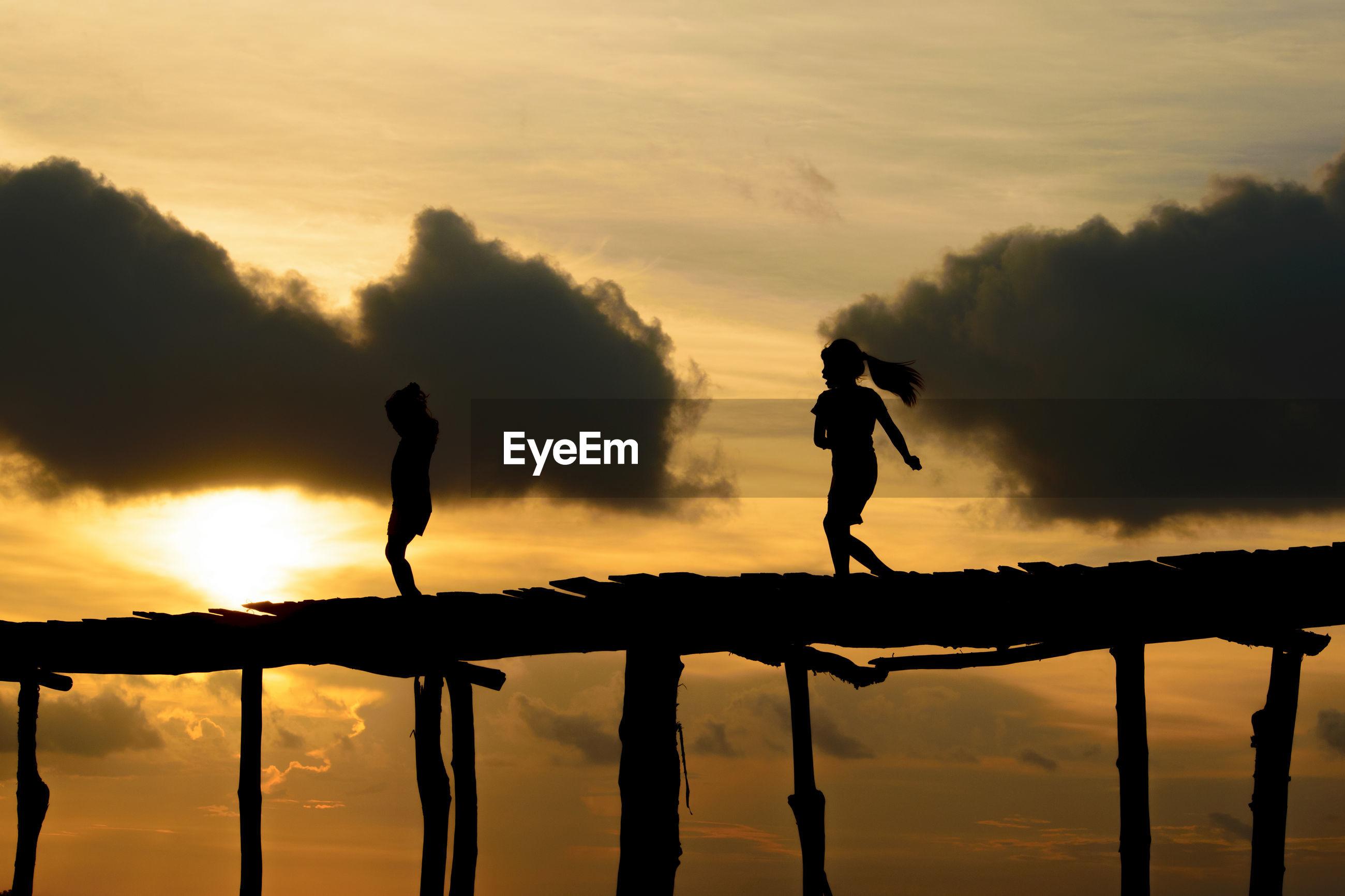 Silhouette girls on footbridge against sky during sunset