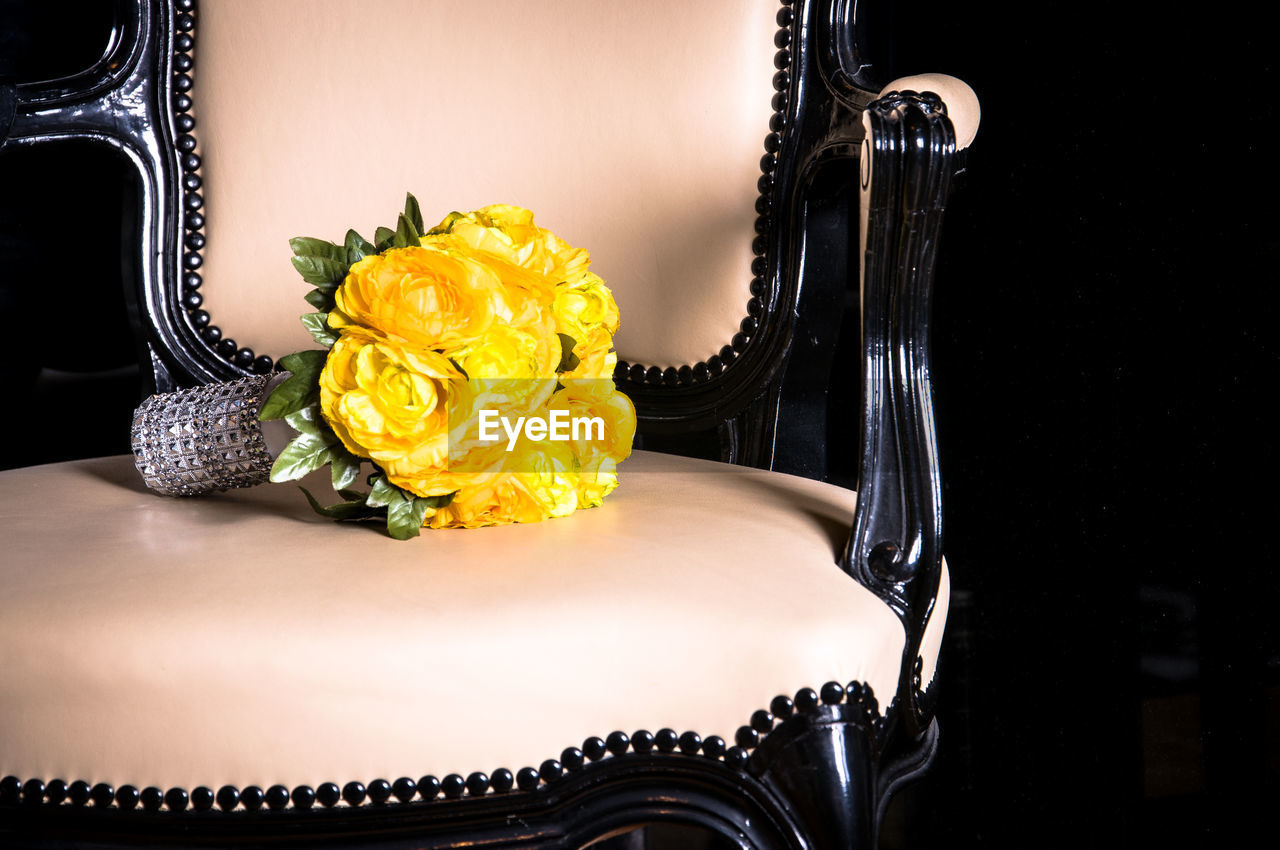 Close-up of bouquet on chair against black background