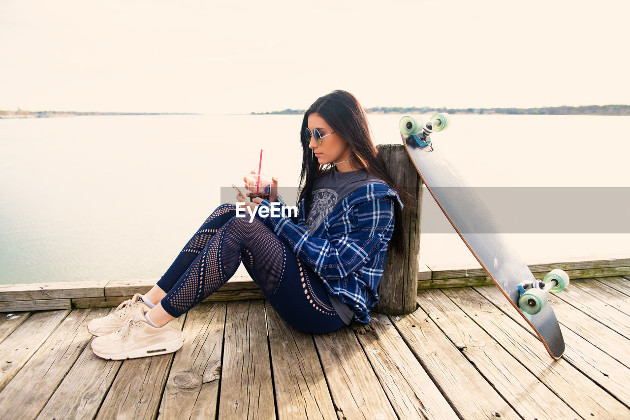 one person, leisure activity, lifestyles, casual clothing, young adult, sitting, real people, young women, full length, wood - material, sky, day, water, women, relaxation, beautiful woman, wood, nature, outdoors, hairstyle