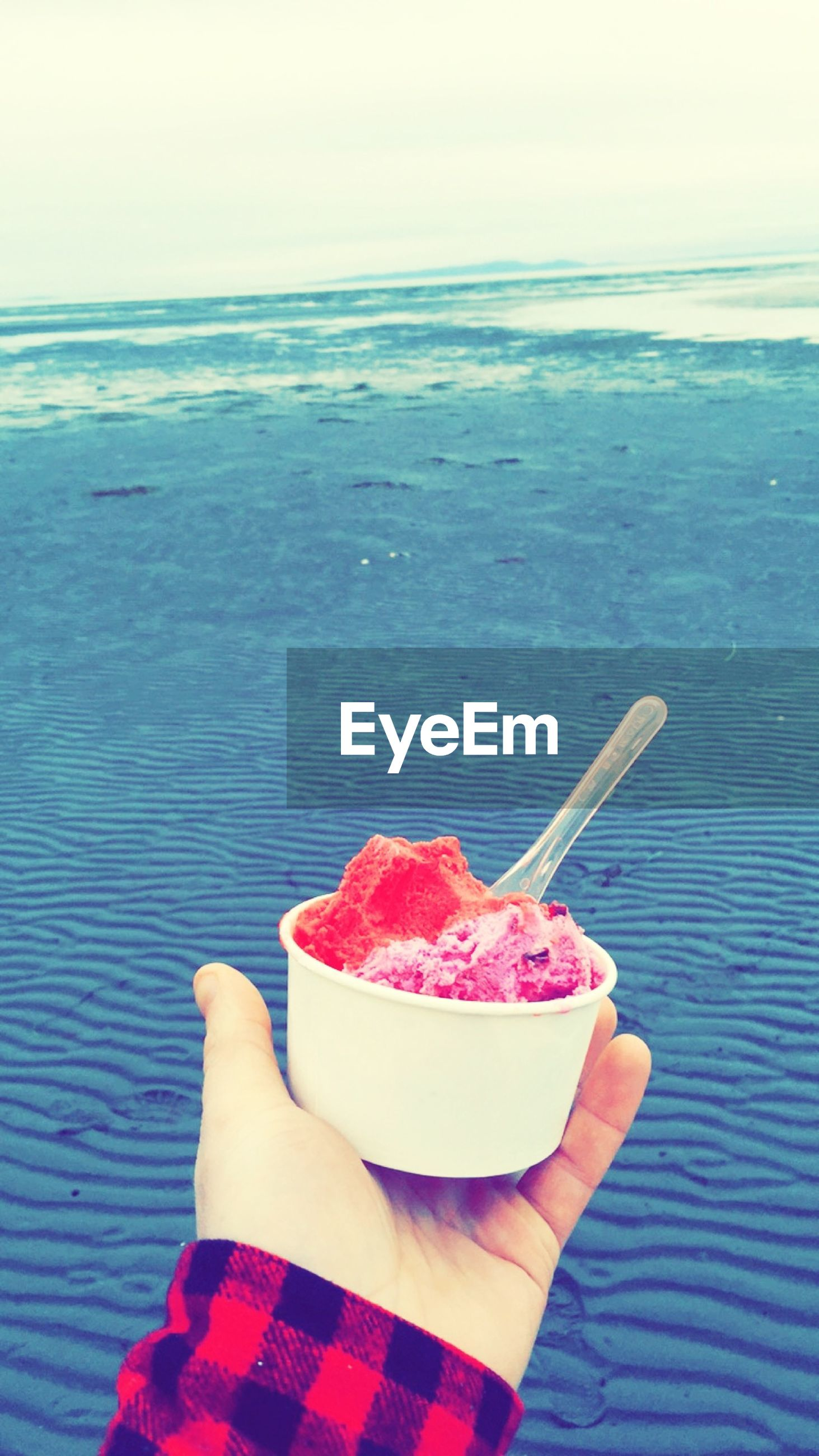 Cropped hand holding ice cream against sea