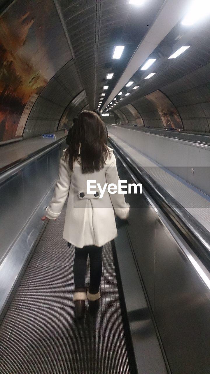 Full length of woman walking on moving walkway