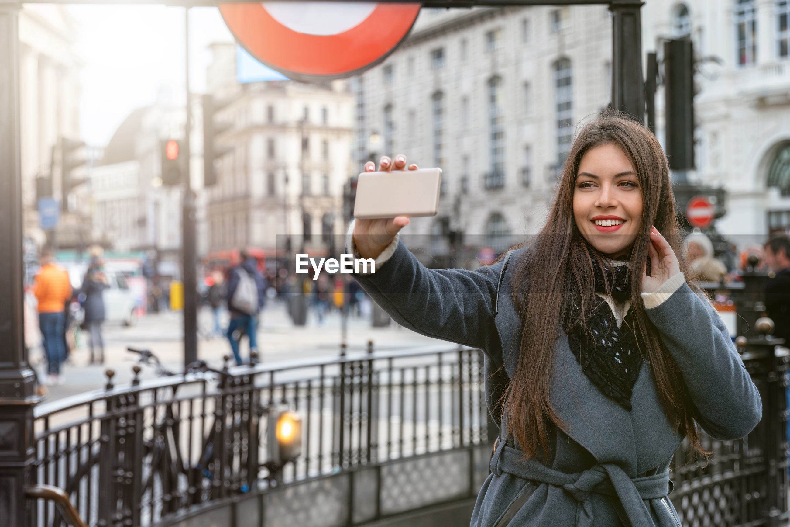 Smiling young woman taking selfie with smart phone in city