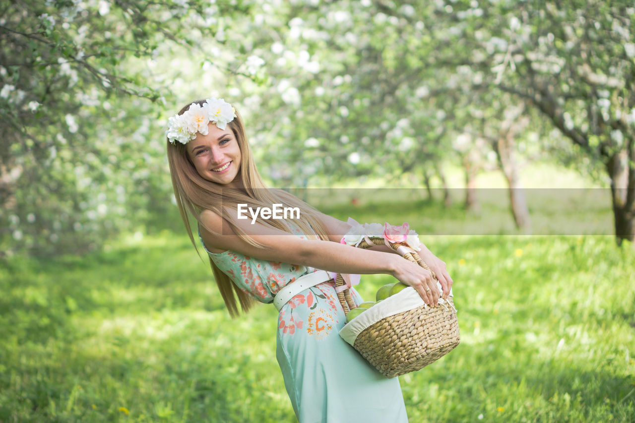 Portrait Of Smiling Woman With Basket Standing On Field