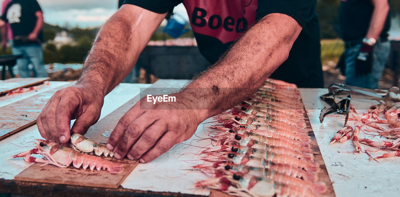 CLOSE-UP OF HANDS PREPARING FOOD ON TABLE
