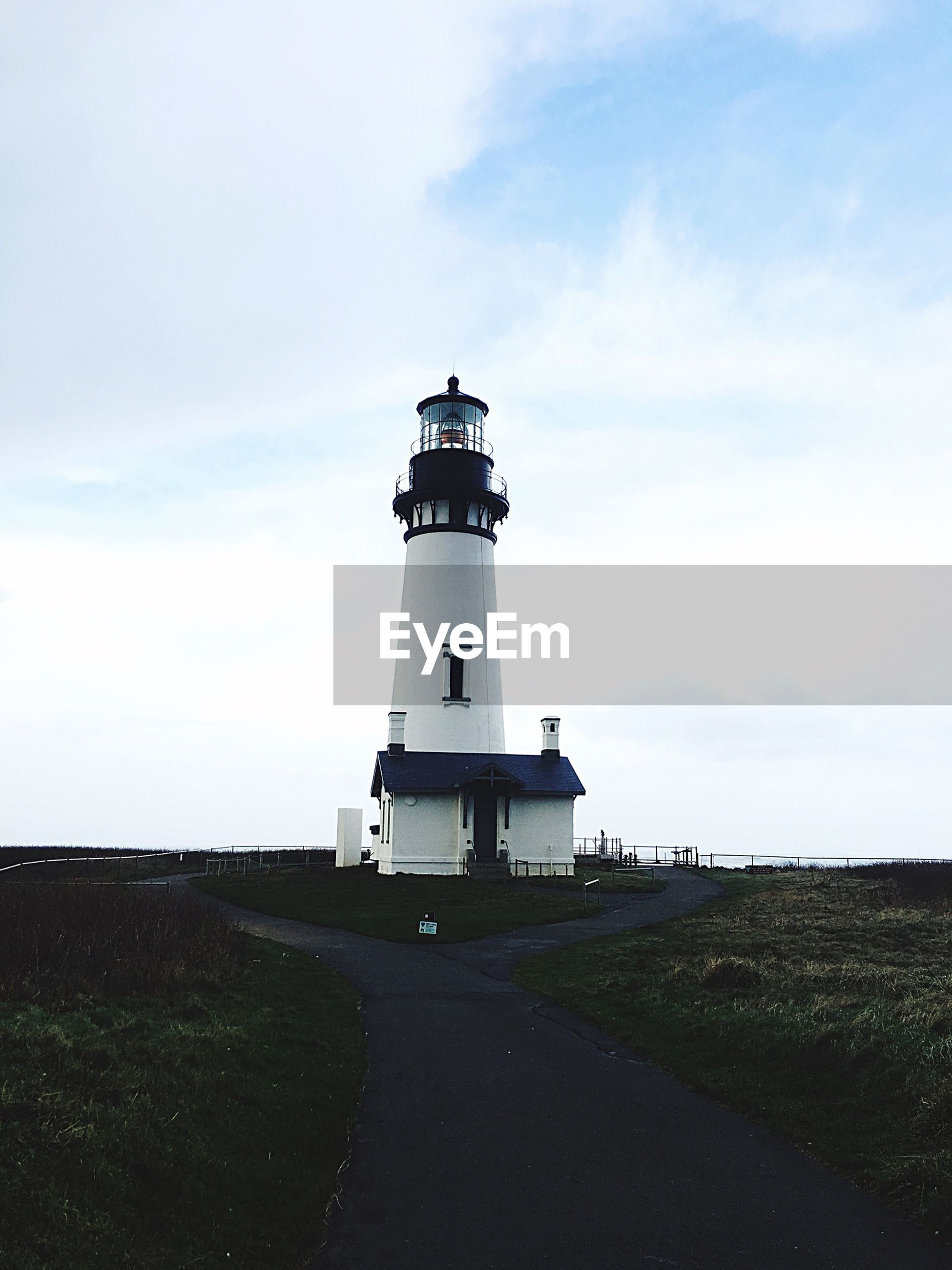 lighthouse, sky, guidance, architecture, building exterior, built structure, direction, safety, protection, cloud - sky, security, cloud, sea, tower, day, nature, tranquility, tranquil scene, field, landscape