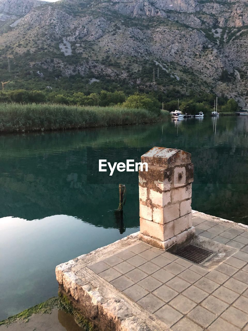 water, lake, nature, architecture, day, mountain, beauty in nature, reflection, built structure, scenics - nature, no people, tranquility, tree, tranquil scene, plant, outdoors, high angle view, travel destinations, building exterior