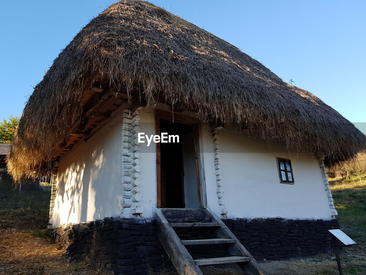 building exterior, built structure, architecture, roof, building, sky, house, no people, nature, clear sky, day, thatched roof, plant, land, residential district, wood - material, low angle view, field, tree, outdoors, cottage