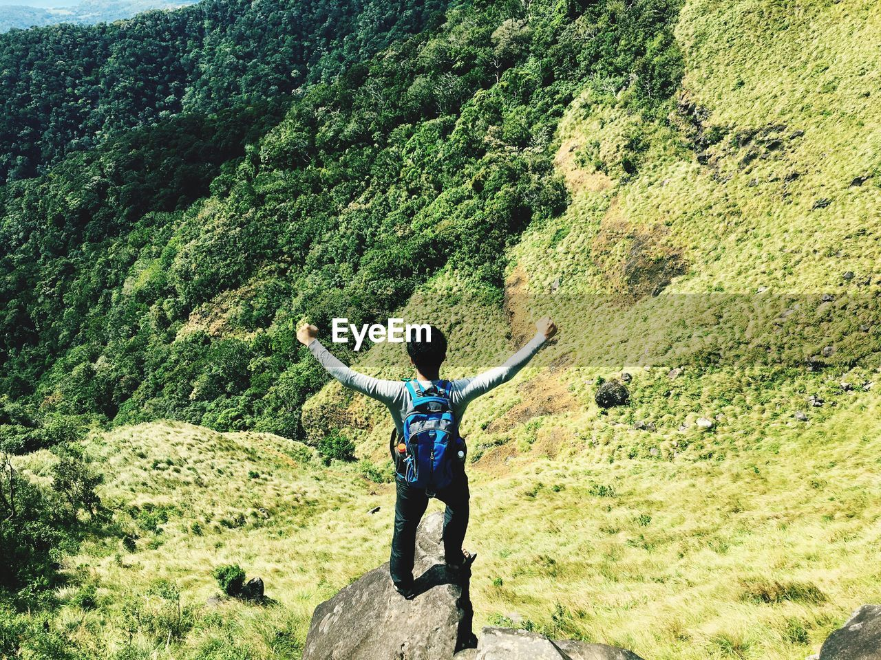 Rear view of man on mountain with arms outstretched
