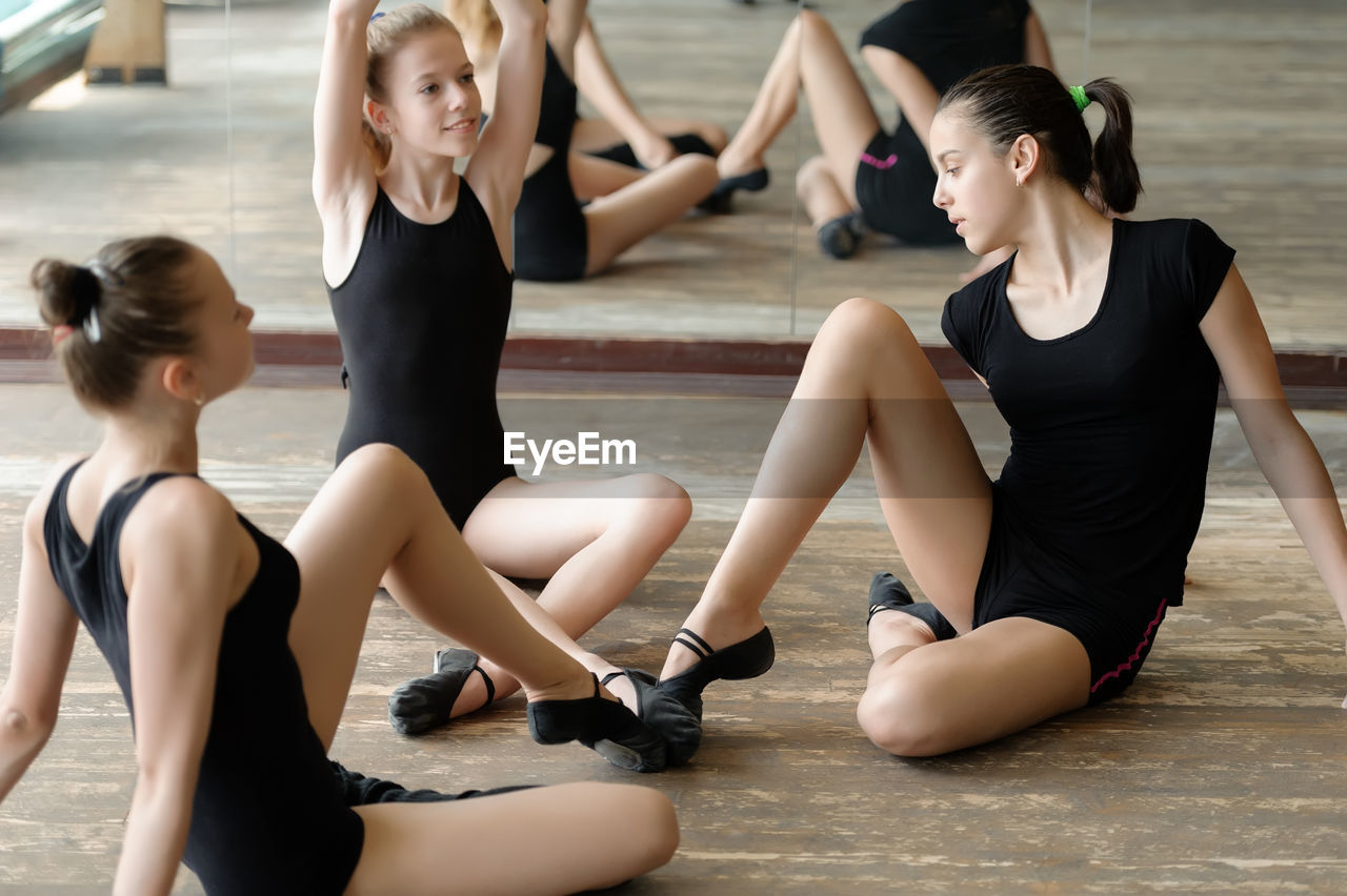practicing, dancing, exercising, lifestyles, group of people, real people, women, dance studio, ballet, indoors, ballet dancer, focus on foreground, flexibility, ballet shoe, skill, healthy lifestyle, young adult, shoe, full length, preparation, teenager