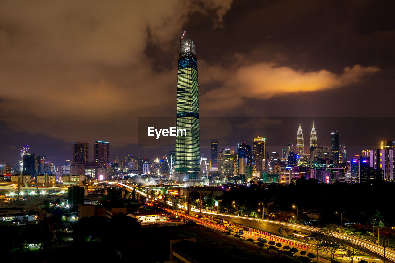 architecture, building exterior, built structure, city, sky, illuminated, tall - high, cloud - sky, night, building, tower, nature, no people, skyscraper, cityscape, office building exterior, travel destinations, office, outdoors, modern, financial district, spire