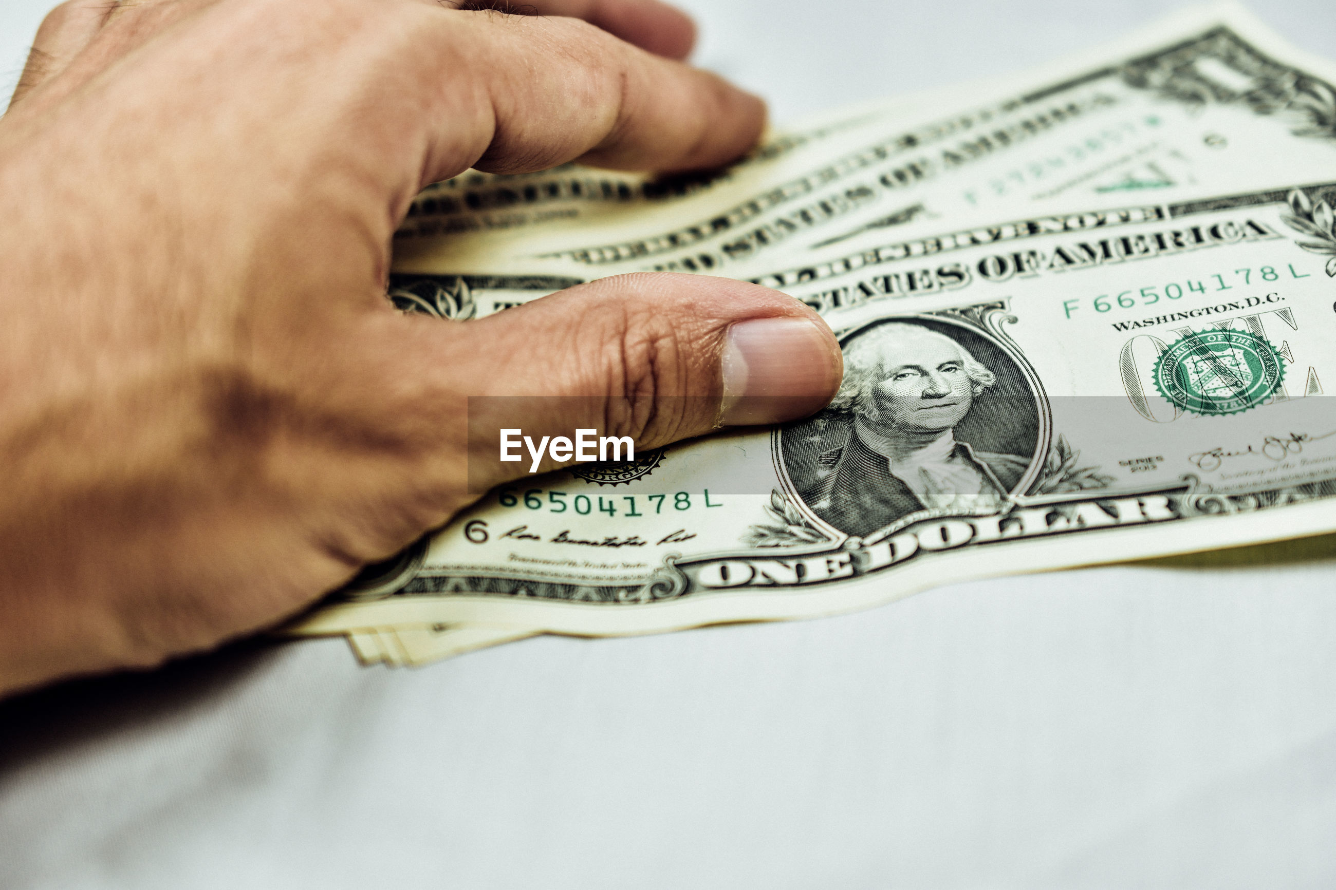 Close-up of human hand holding paper currencies on table