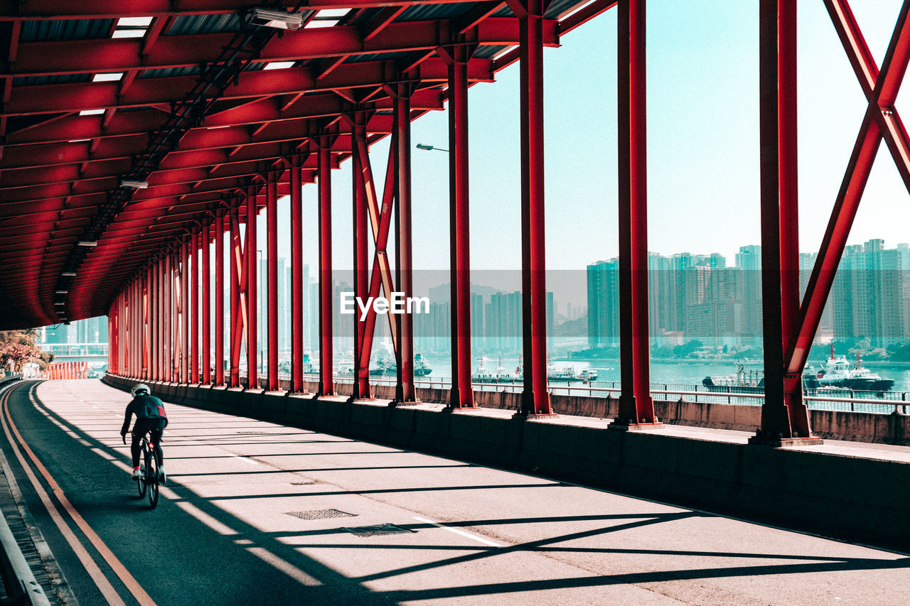 Rear View Of Man Riding Bicycle Below Bridge In City
