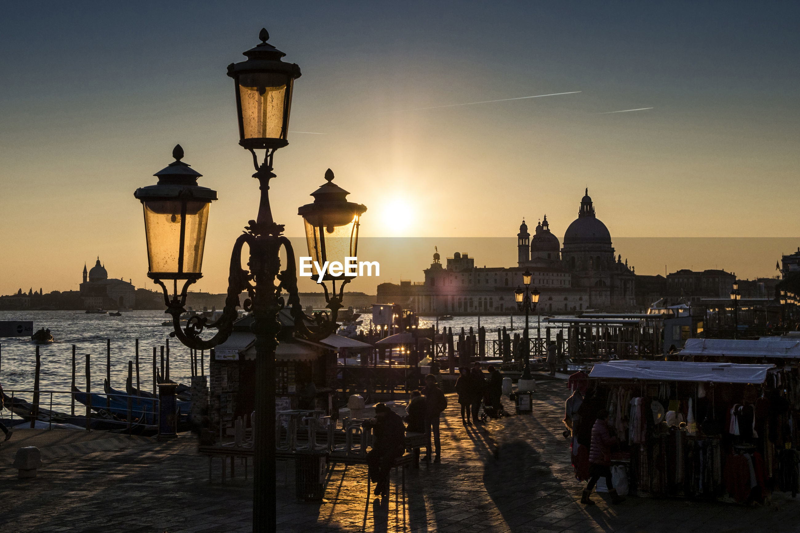 Gas light and people on promenade by grand canal with santa maria della salute during sunset