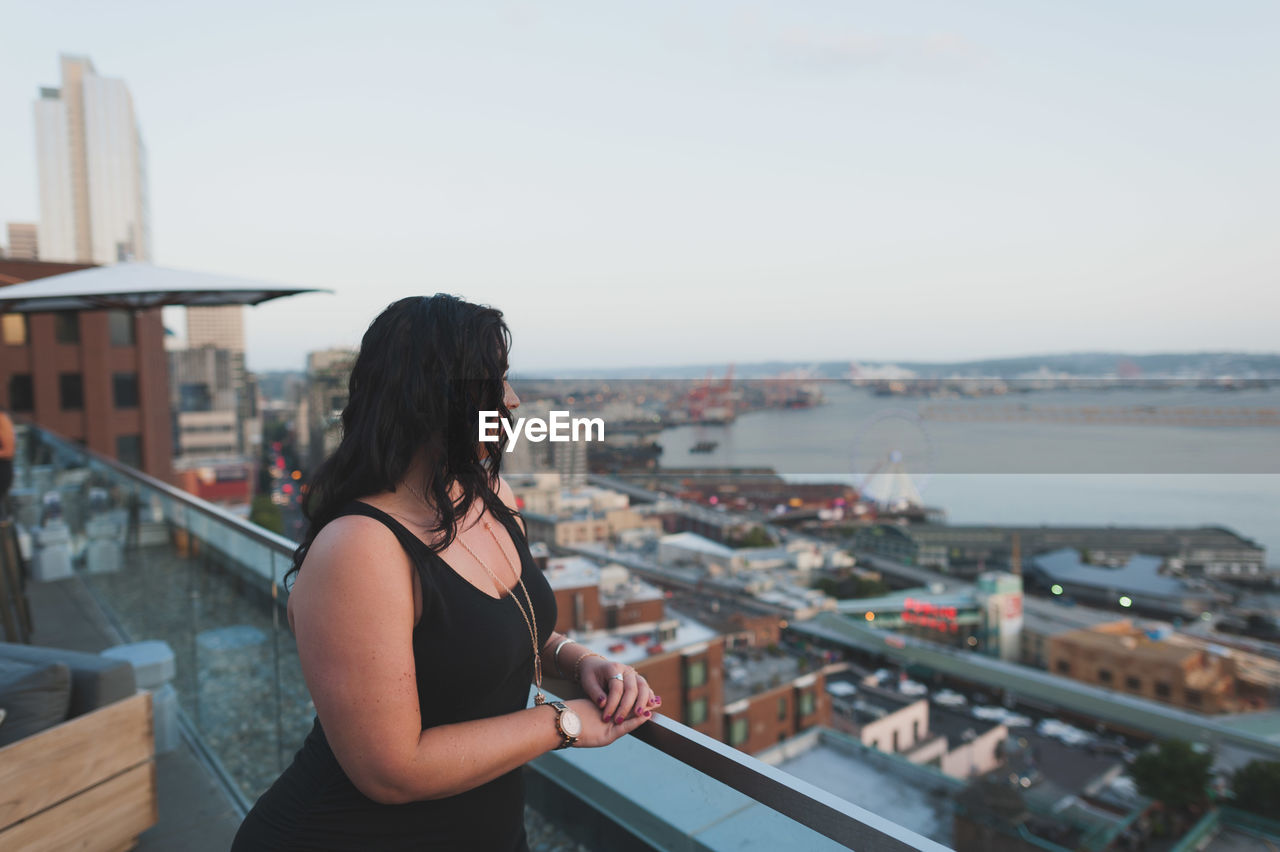 Woman Standing By Railing Against Sky