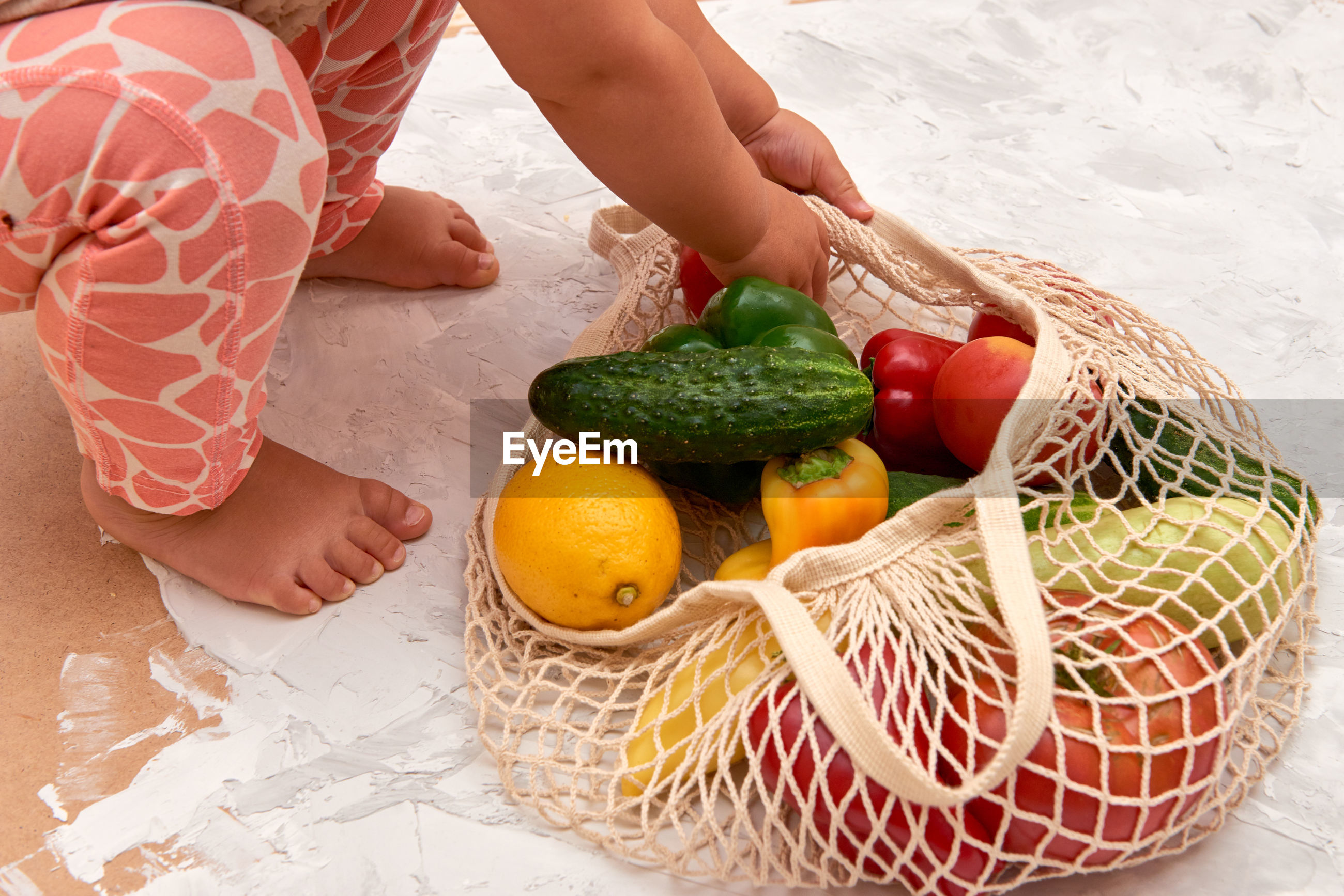 HIGH ANGLE VIEW OF WOMAN WITH VEGETABLES ON BASKET