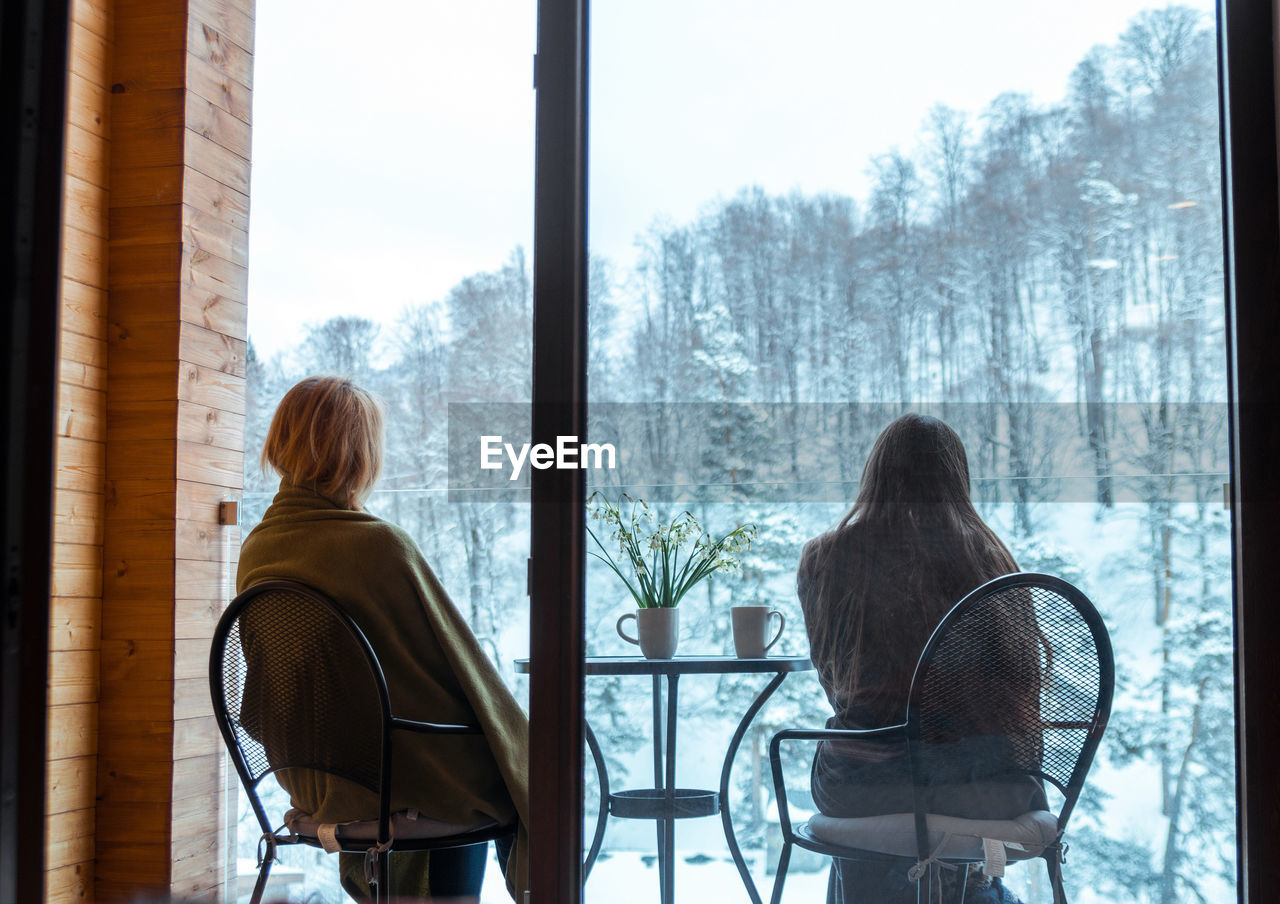 Rear view of woman sitting at table during winter