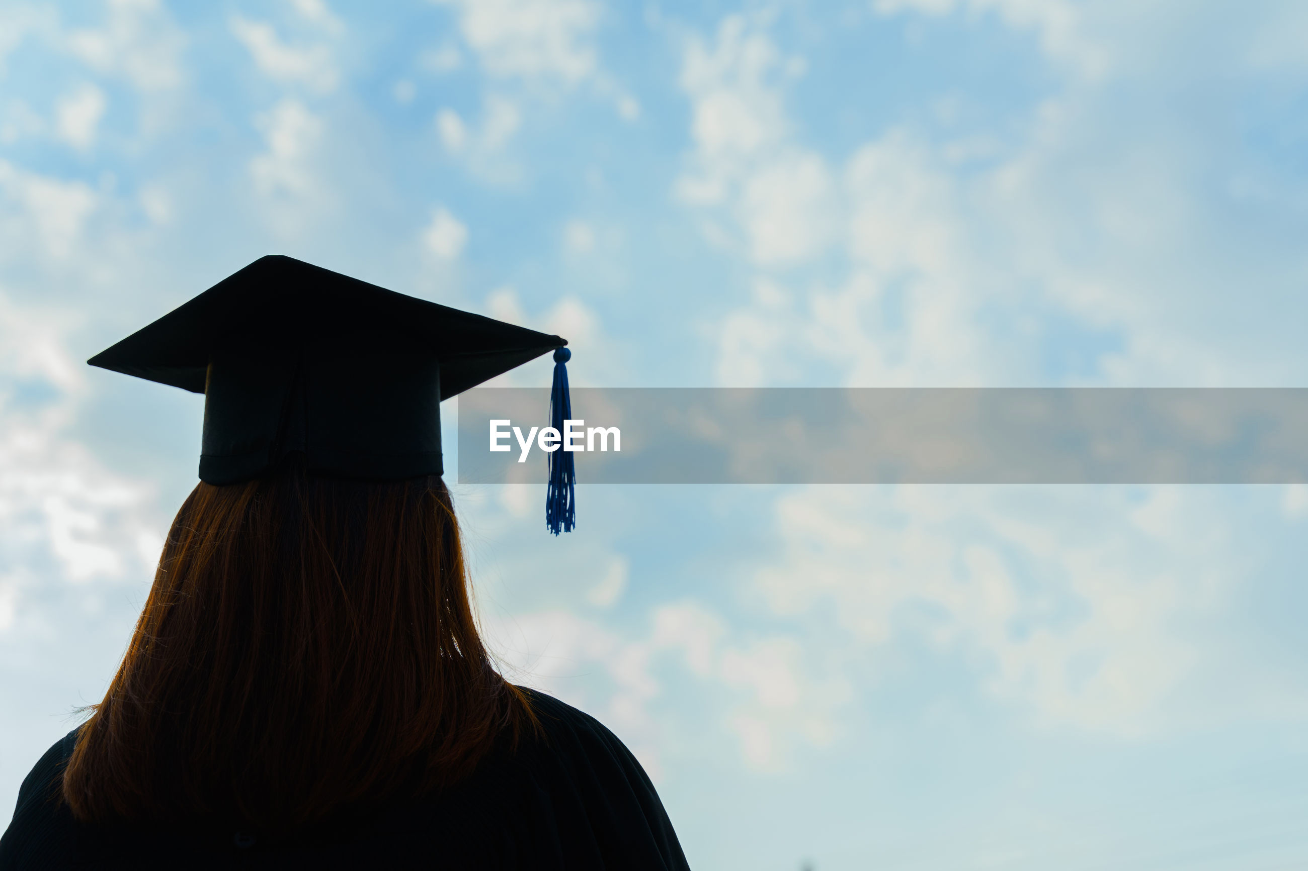 Rear view of woman with mortarboard against sky