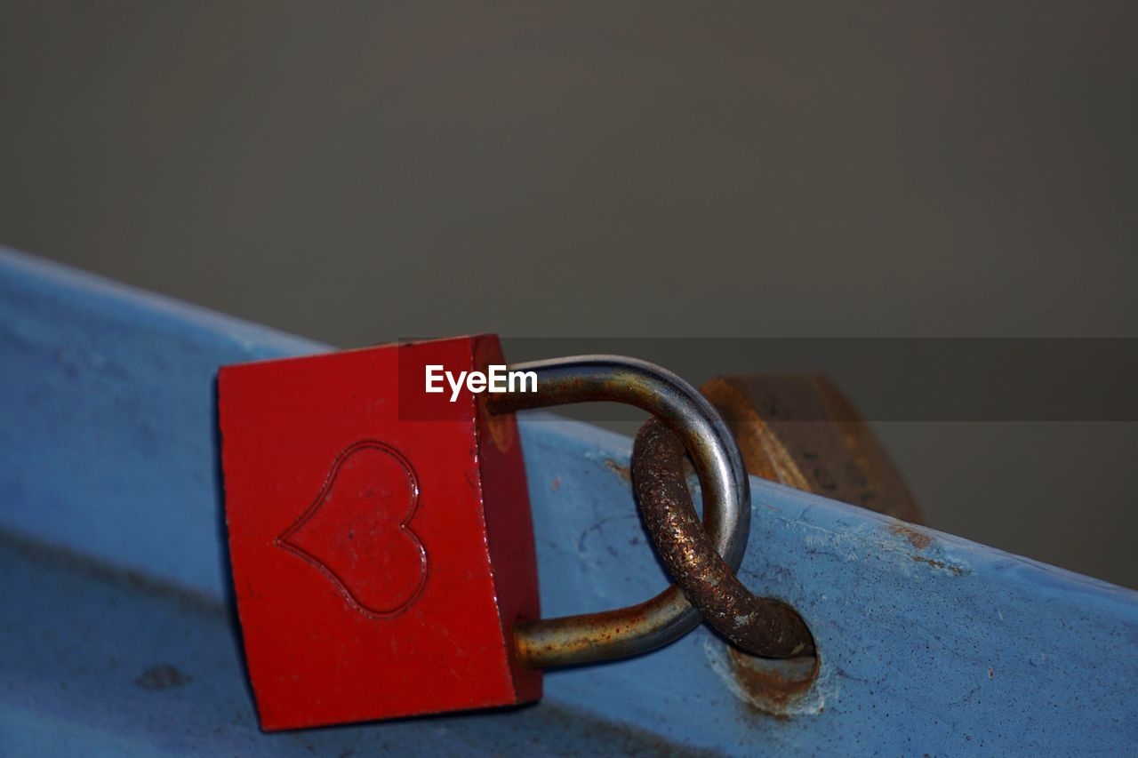 Close-Up Of Red Padlock With Heart Shape Attached In Railing