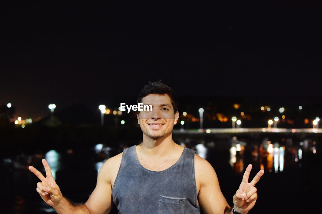 Portrait Of Man Smiling While Gesturing Peace Sign In City At Night