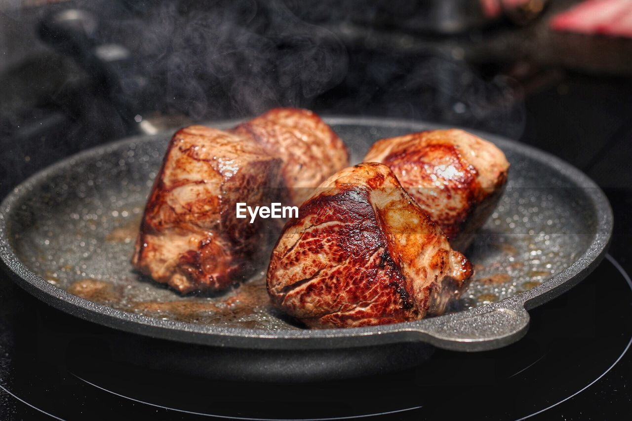 Close-Up Of Beef Steak On Frying Pan
