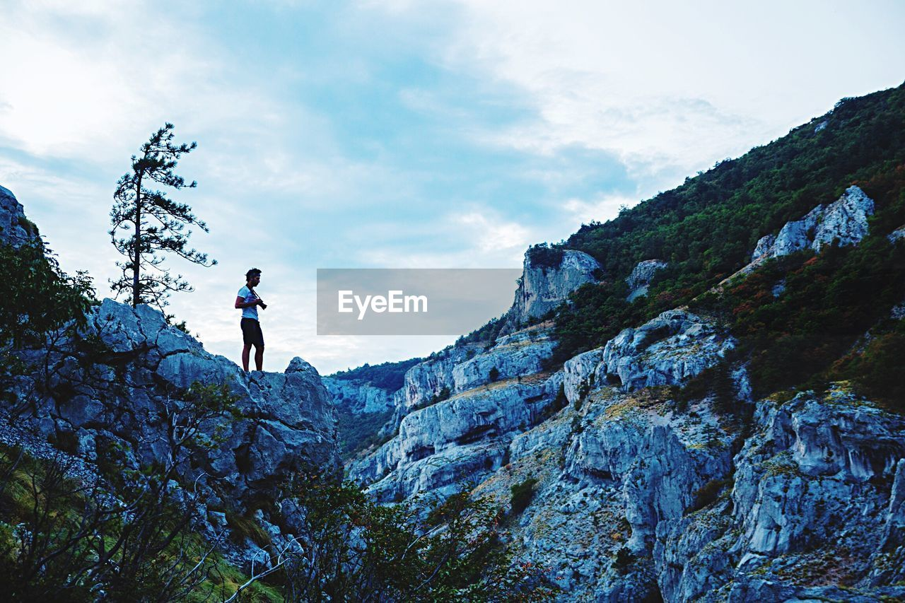 mountain, real people, adventure, rock - object, sky, cloud - sky, nature, lifestyles, leisure activity, hiking, one person, full length, scenics, low angle view, men, outdoors, healthy lifestyle, beauty in nature, day, climbing, cliff, mountain range, standing, extreme sports, one man only, adult, people
