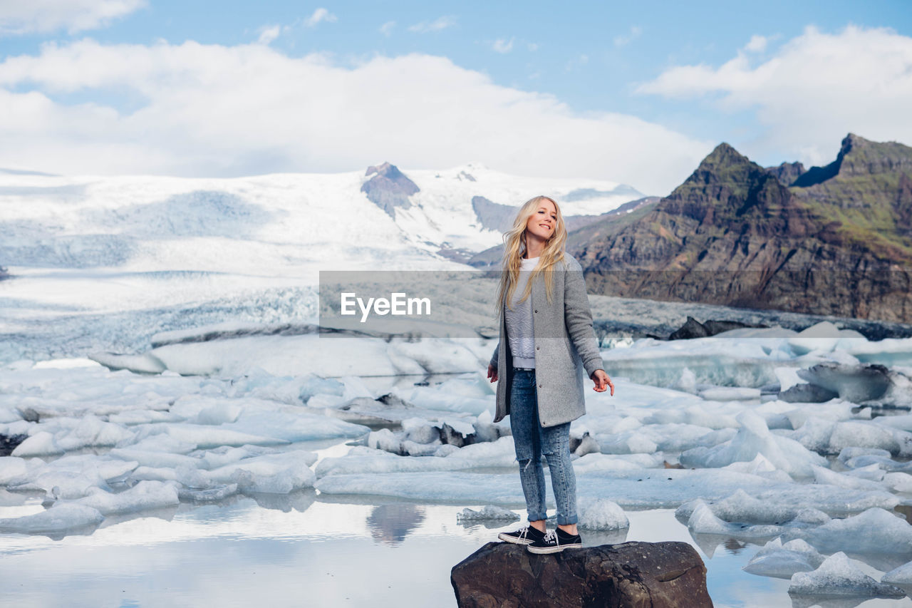 Woman Standing On Snow Covered Landscape Against Mountains