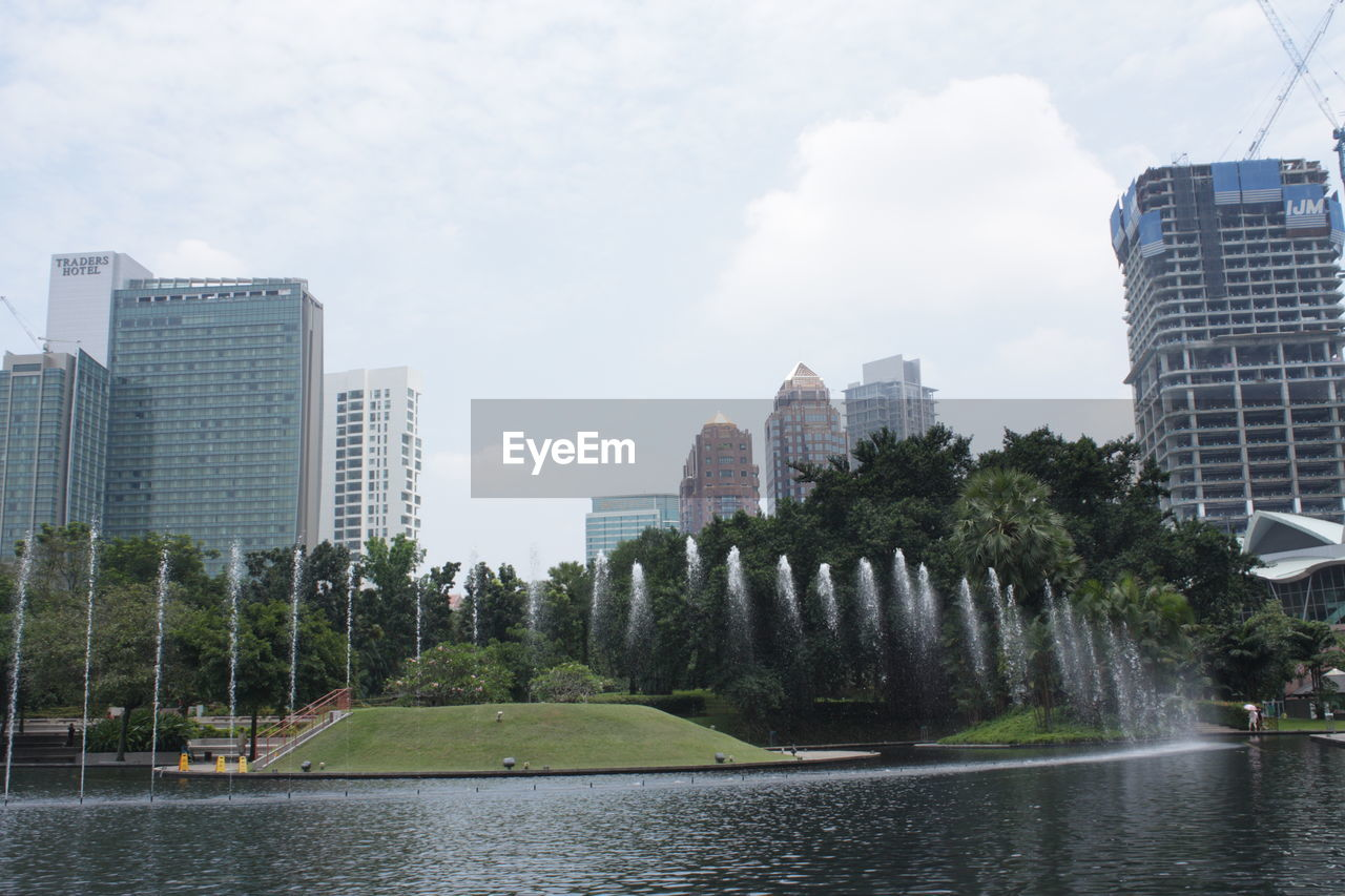 architecture, built structure, building exterior, city, water, building, sky, plant, nature, tree, office building exterior, waterfront, river, skyscraper, day, urban skyline, no people, growth, modern, cityscape, outdoors, high, financial district