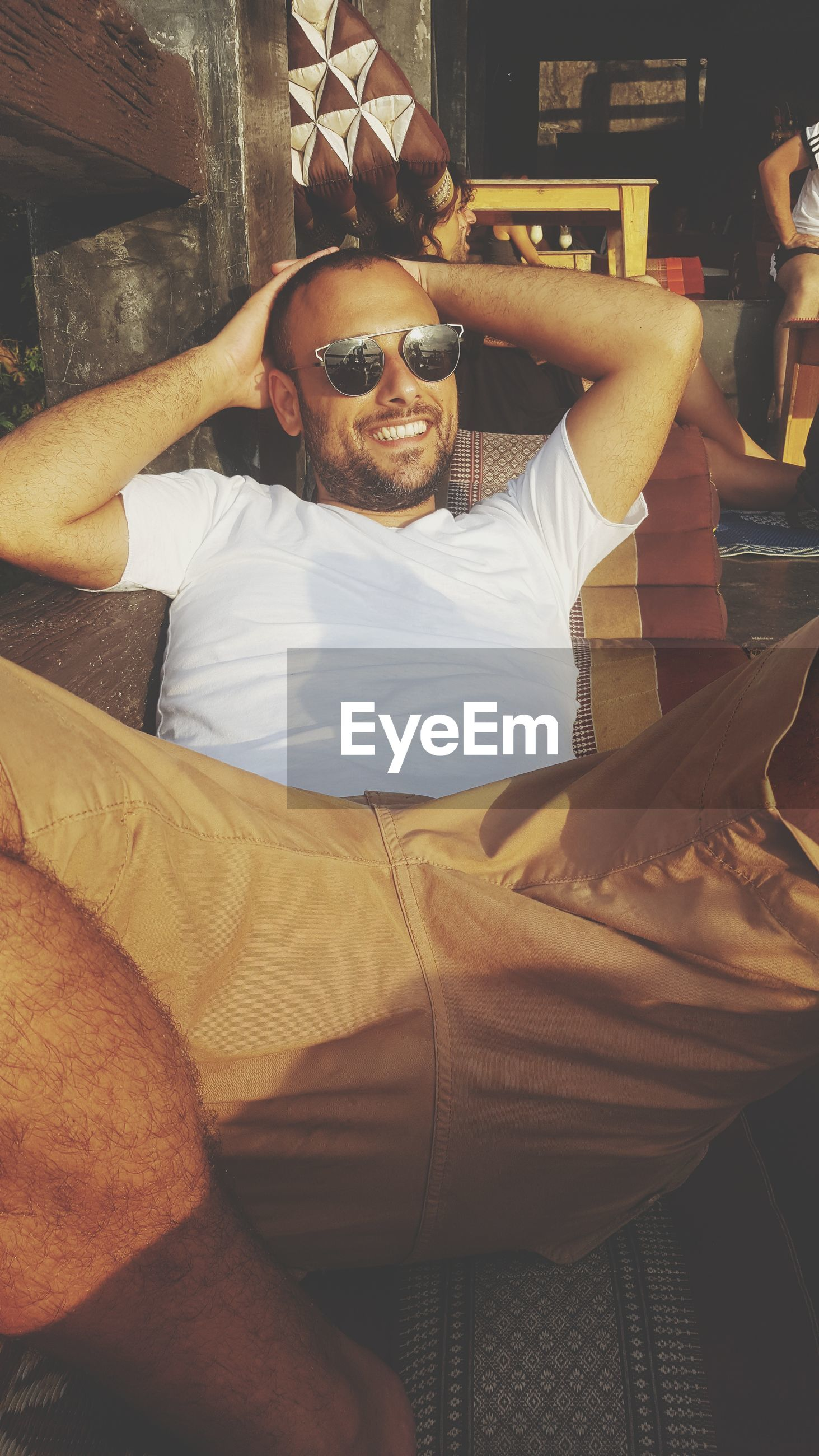 one person, real people, casual clothing, sunglasses, sitting, mid adult men, looking at camera, relaxation, happiness, home interior, front view, leisure activity, lifestyles, mature men, portrait, smiling, beard, indoors, comfortable, men, full length, day, bed, hands behind head, young adult, home showcase interior, one man only, people