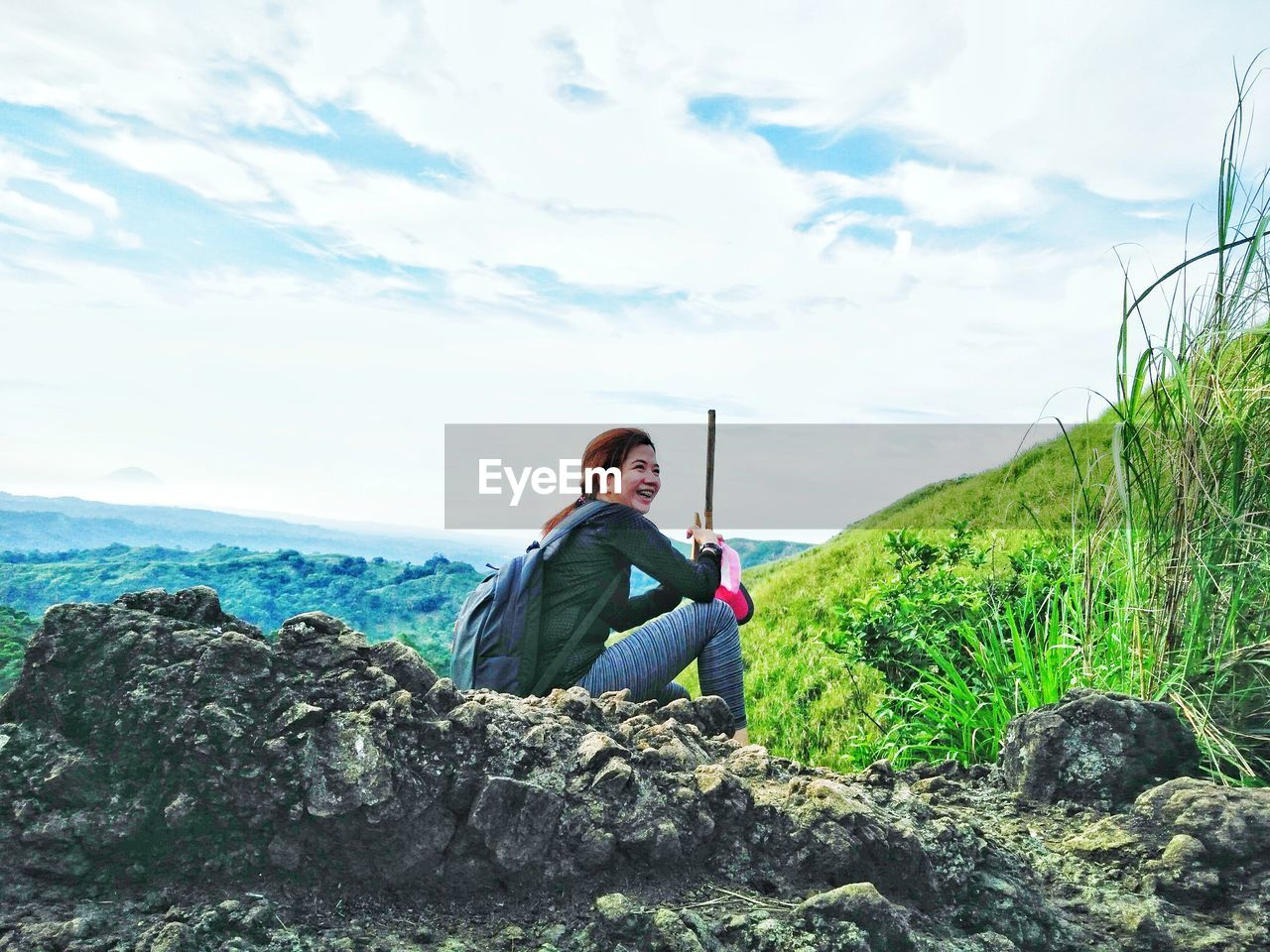 Side view of cheerful female hiker sitting on rocky cliff against cloudy sky