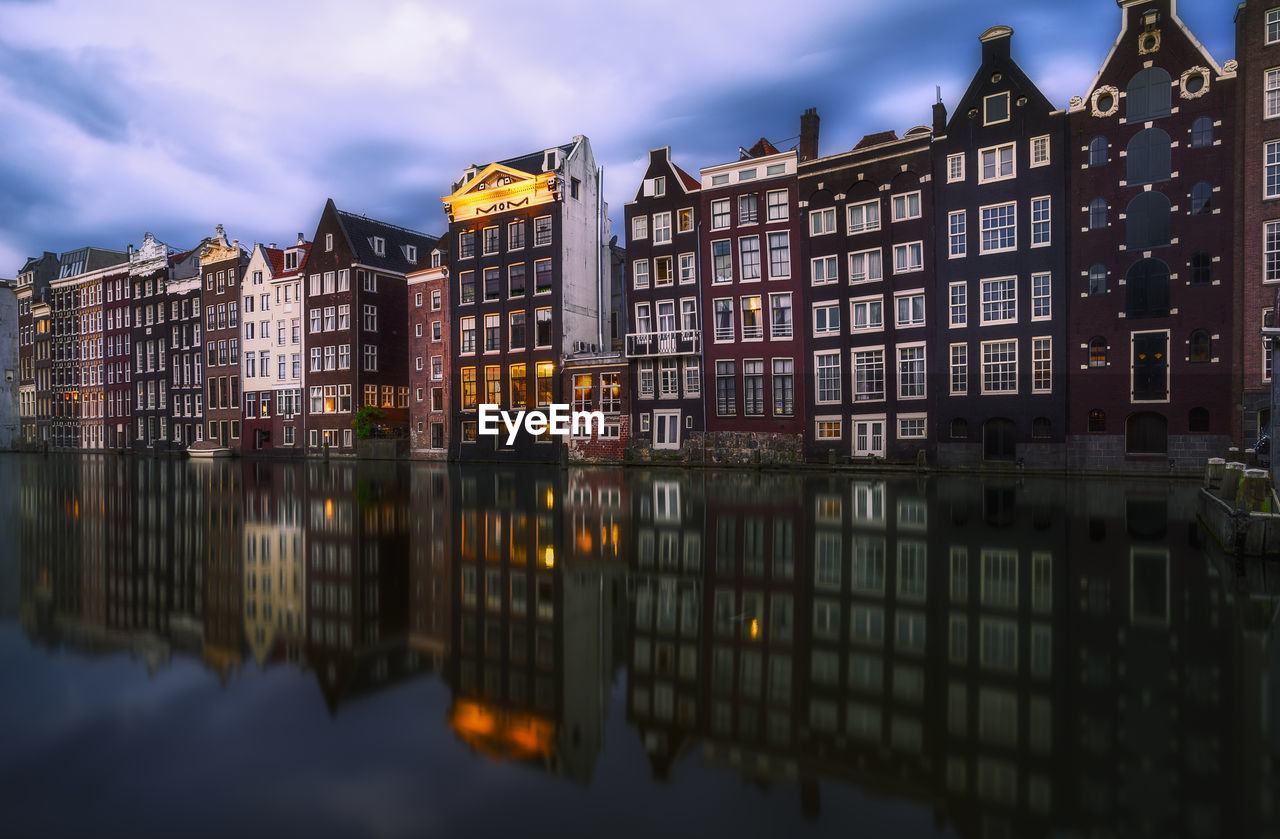 Reflection Of Buildings On River In City