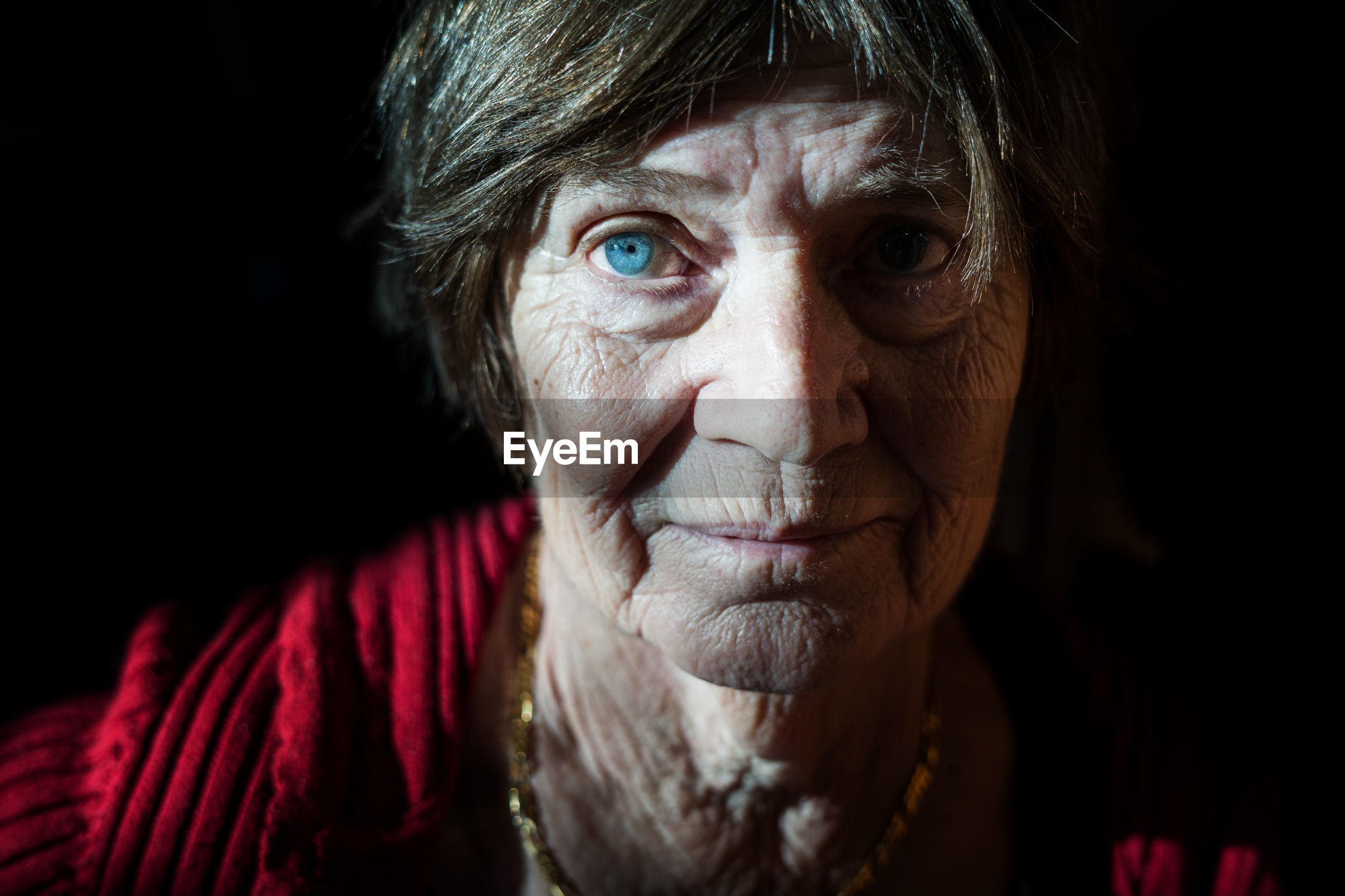Close-up portrait of senior woman against black background