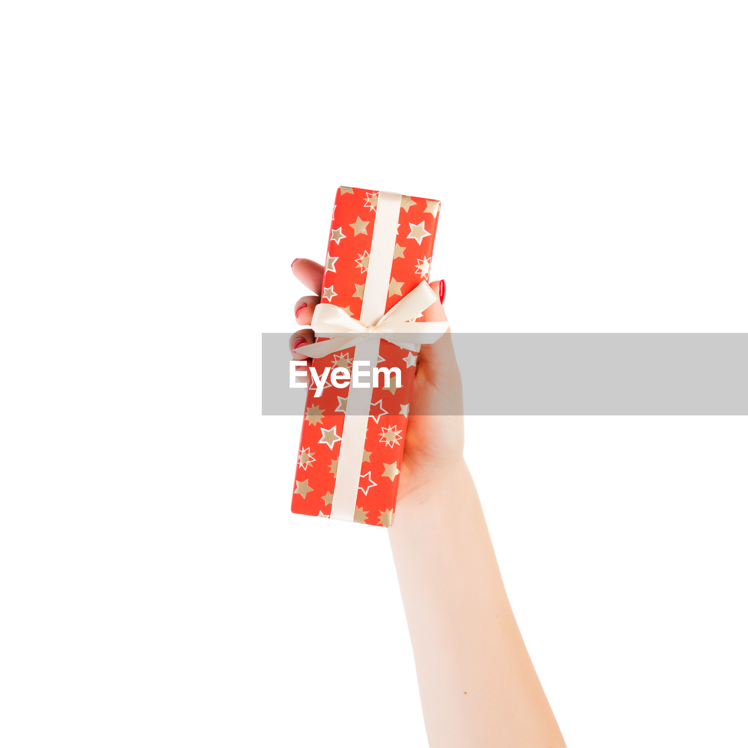 Close-up of hand holding gift against white background