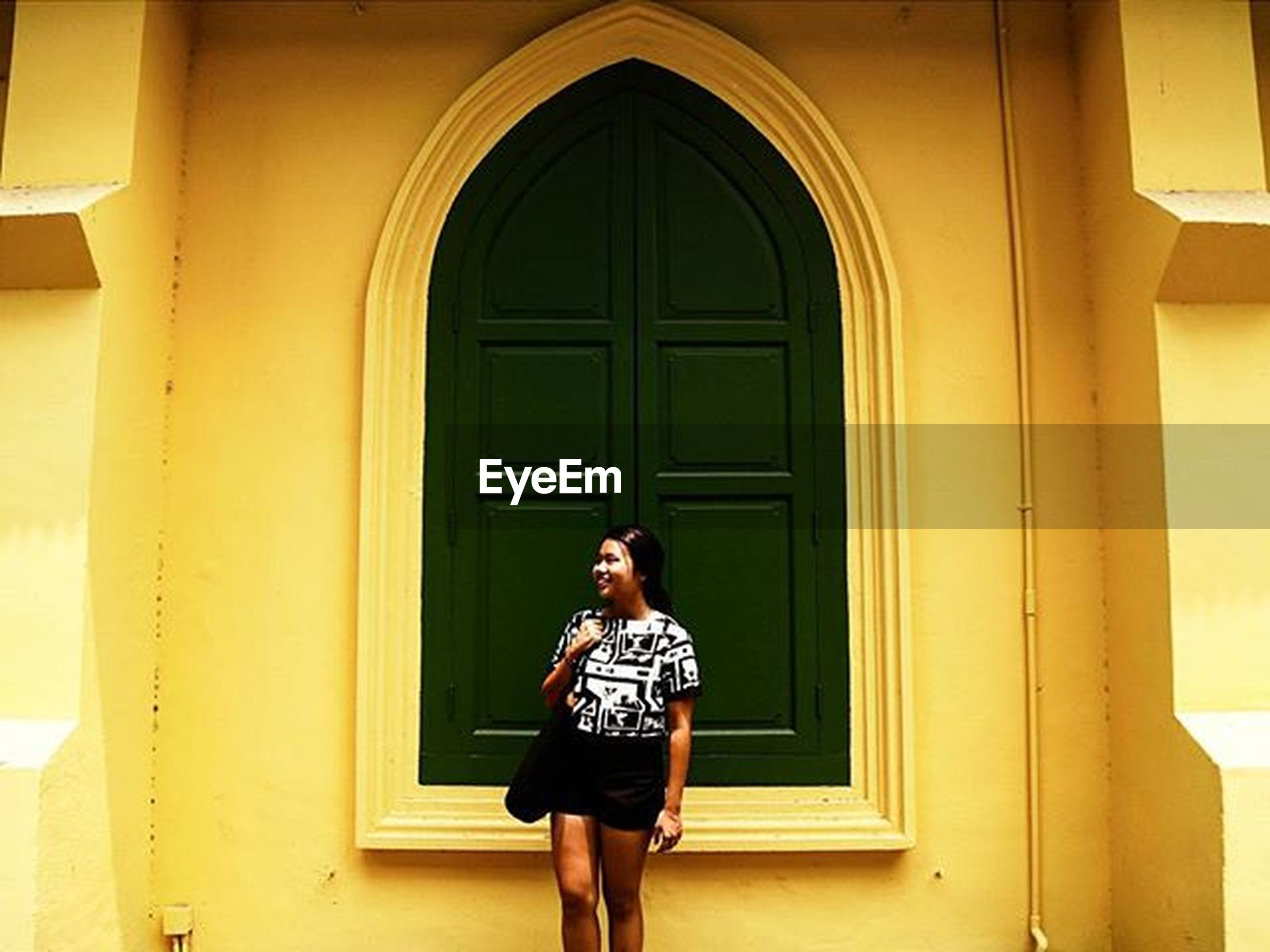 door, lifestyles, standing, architecture, built structure, window, full length, casual clothing, young adult, building exterior, front view, house, closed, leisure activity, young women, entrance, three quarter length, doorway