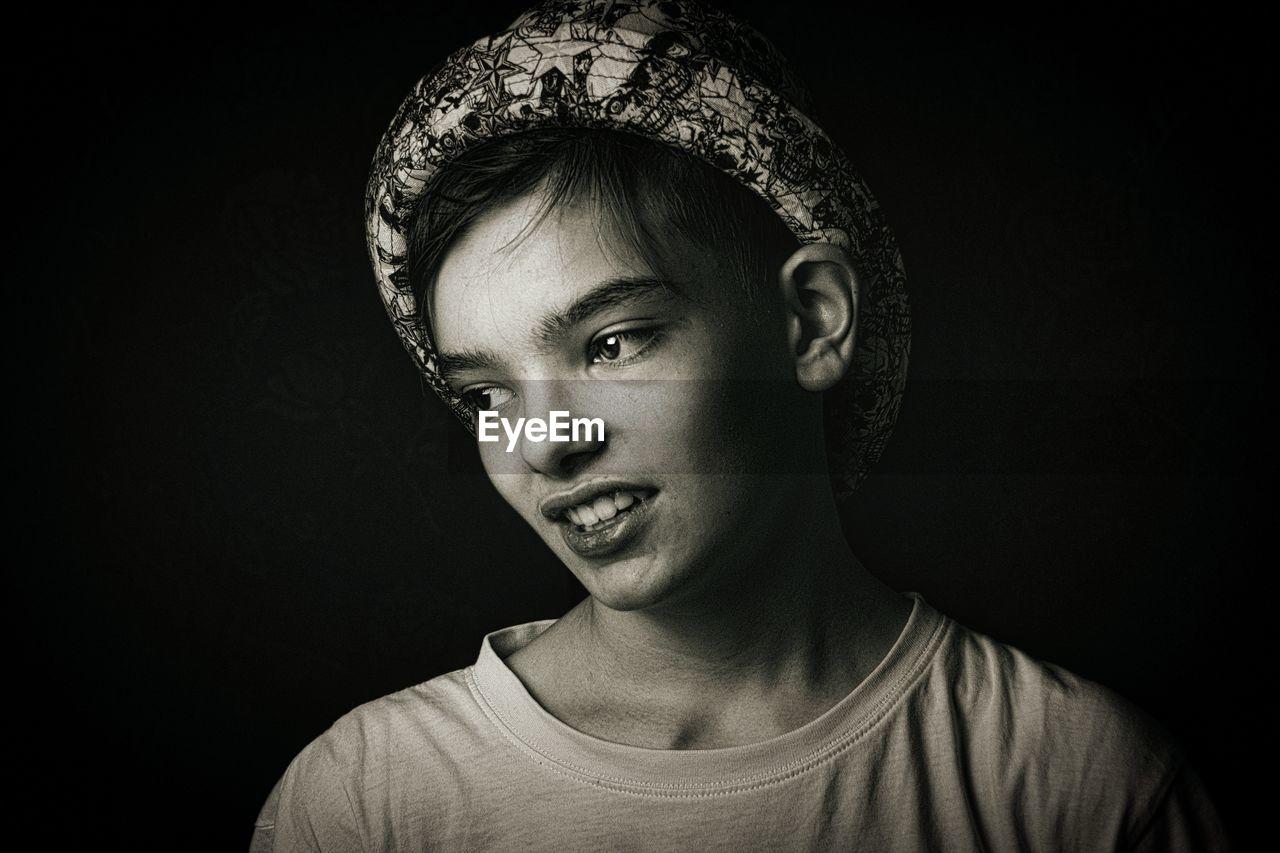 Close-up of teenage boy against black background