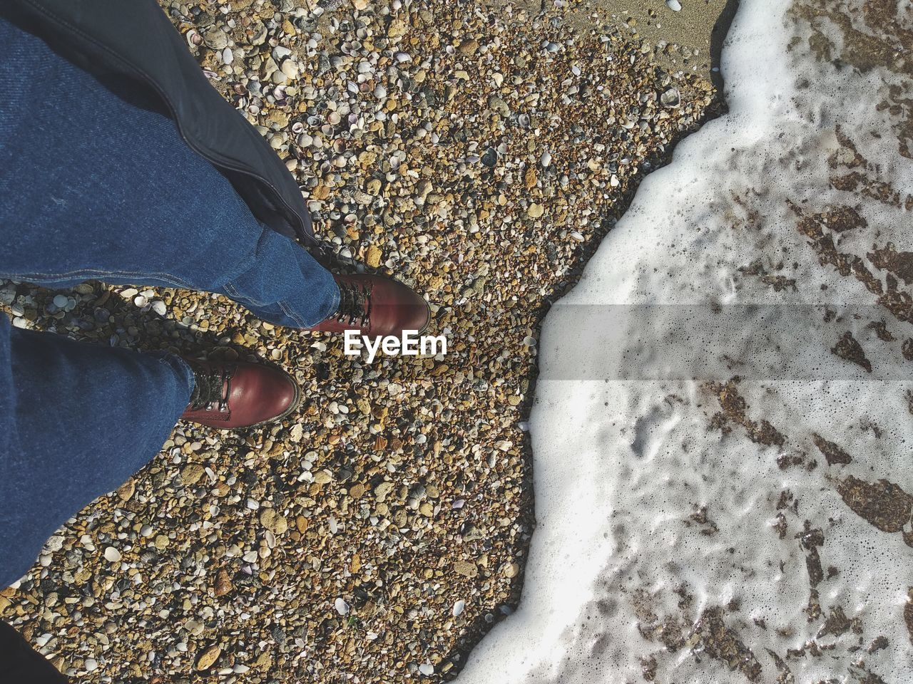 low section, human leg, human body part, real people, body part, shoe, standing, one person, lifestyles, high angle view, surfing, water, leisure activity, day, aquatic sport, nature, snow, land, human foot, outdoors, pebble, human limb