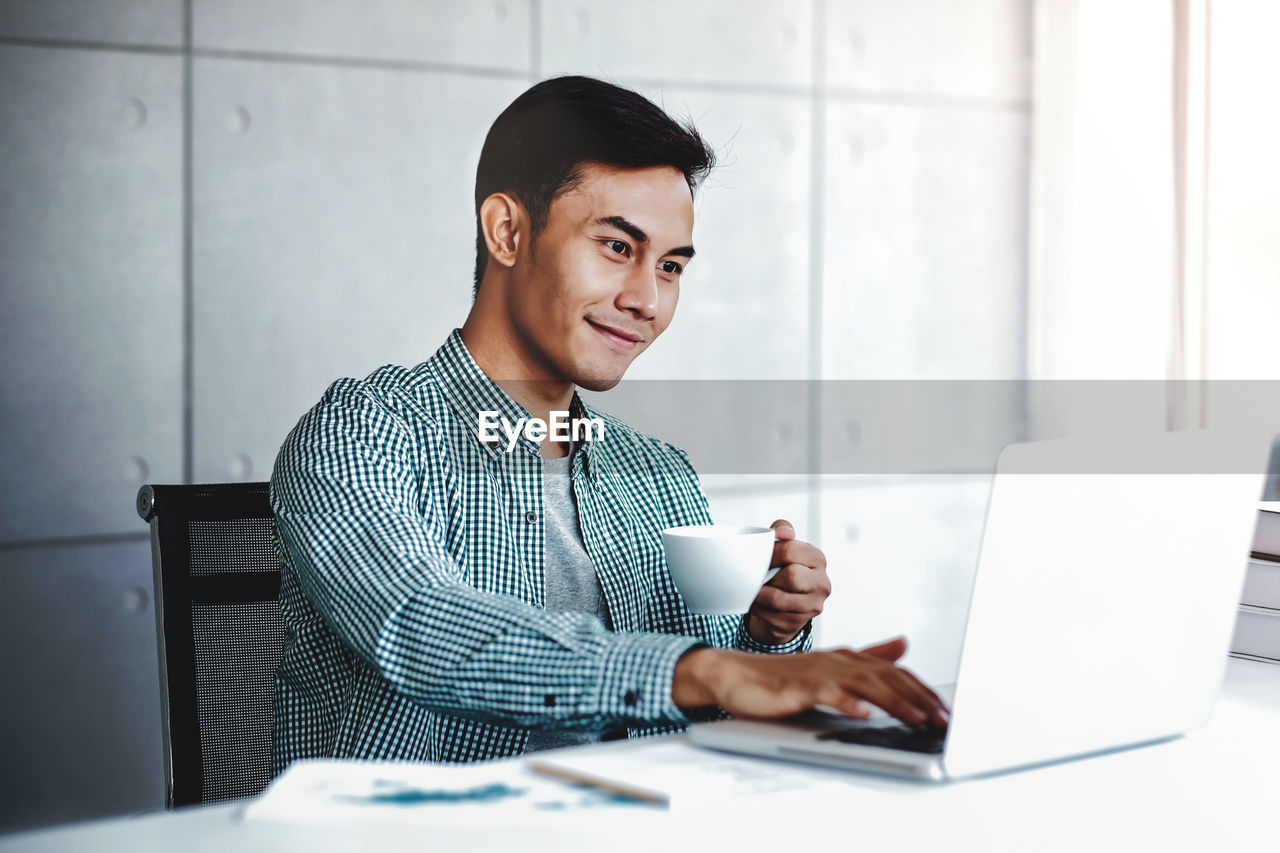 one person, young men, young adult, laptop, technology, computer, wireless technology, indoors, communication, sitting, men, table, real people, business person, waist up, office, smiling, business, using laptop, new business, entrepreneur
