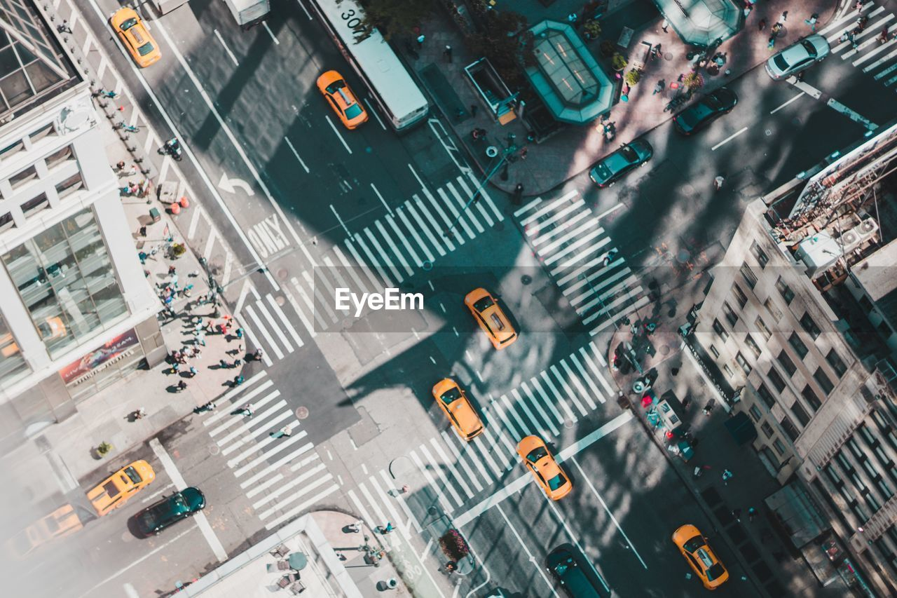 city, transportation, street, road, traffic, car, architecture, motor vehicle, city street, mode of transportation, zebra crossing, crossroad, crosswalk, city life, road marking, crossing, building exterior, high angle view, sign, on the move, road intersection, outdoors, cityscape